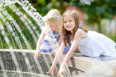 Dwa ślicznej małej dziewczynki bawić się z miasto fontanną na gorącym letnim dniu Zdjęcie Royalty Free