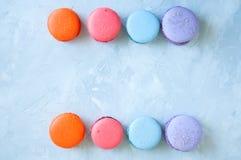 Dwa linii kolorowi macarons na białym kamiennym tle clos Fotografia Stock