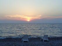 Dwa loungers na morze plaży przy zmierzchem Obraz Royalty Free