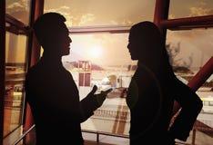 Dwa ludzie biznesu opowiada w lotnisku, sylwetka fotografia stock
