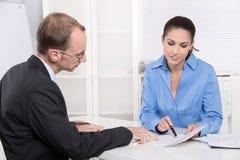 Dwa ludzie biznesu opowiada wpólnie przy biurkiem - doradca i custo zdjęcia stock