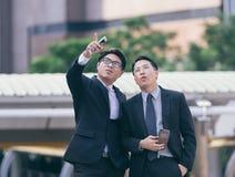 Dwa ludzie biznesu przyglądający up przedstawienia i punktu wierzch Zdjęcia Royalty Free