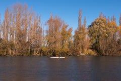 Dwa ludzie na kajaku płyną na Waimakariri rzece przy jesienią Zdjęcie Stock