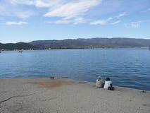 Dwa ludzie siedzi na doku zdjęcie stock