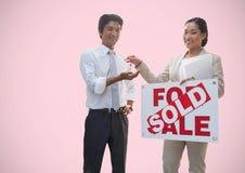 Dwa ludzie trzyma Dla sprzedaży podpisują i klucze przed winietą Zdjęcie Stock