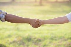 Dwa ludzie uścisku dłoni w ogrodowych polach Obrazy Royalty Free