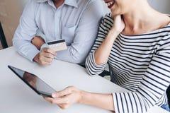 Dwa ludzie używa pastylkę, kredyt i kart debetowych metrykalne zapłaty/ Zdjęcia Royalty Free