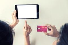 Dwa ludzie używa pastylkę, kredyt i kart debetowych metrykalne zapłaty/ Zdjęcie Royalty Free