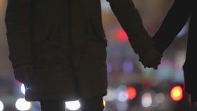 Dwa ludzie w miłości trzyma ręki, chodzi wolno wzdłuż ruchliwie miasto ulicy przy nocą zdjęcie wideo