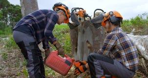 Dwa lumberjacks nalewa olej na butelce 4k zbiory wideo