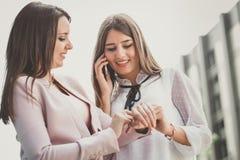 Dwa młodej biznesowej kobiety układają spotkania przez telefonu komórkowego fotografia royalty free
