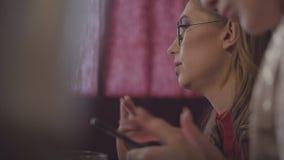 Dwa młodej pięknej kobiety gawędzą podczas gdy siedzący przy stołem w restauracji Jeden dziewczyny używa internet wewnątrz zdjęcie wideo