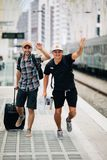 Dwa mężczyzn podróżnika chybienie po pociągu na platformie na stacji kolejowej lub opóźniony na pociągu i bieg samochodowej miast obraz royalty free