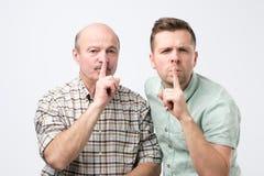 Dwa mężczyzn utrzymania pierwszego planu dojrzały palec na wargach, próby utrzymywać spisek fotografia stock