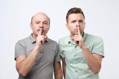 Dwa mężczyzn utrzymania pierwszego planu dojrzały palec na wargach, próby utrzymywać spisek obrazy stock