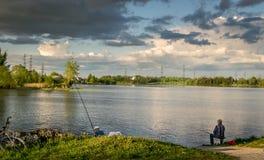 Dwa mężczyzna łowi w jeziorze z burz chmurami zdjęcie royalty free