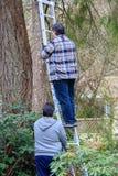 Dwa mężczyzna chwyta wspinaczka dla pracy i drabina zdjęcia stock