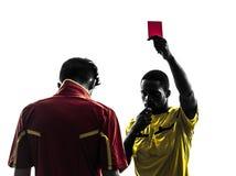 Dwa mężczyzna gracz piłki nożnej i arbiter pokazuje czerwonej kartki sylwetkę fotografia stock