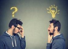 Dwa mężczyzna myśleć jeden pytanie inny rozwiązanie z żarówki above głową Zdjęcie Royalty Free