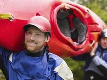 Dwa mężczyzna niesie kajaka outdoors Fotografia Stock
