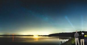 Dwa mężczyzna obserwuje pięknego Milky sposób błyszczeć nad jeziorem Zdjęcie Royalty Free