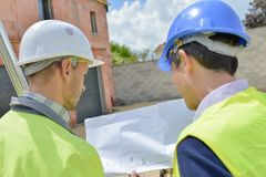 Dwa mężczyzna patrzeje plany na placu budowy Obraz Stock