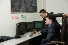 Dwa mężczyzna pracuje wpólnie dla komputerów w biurze angażowali w handlu Obraz Stock
