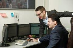 Dwa mężczyzna pracuje wpólnie dla komputerów w biurze angażowali w handlu Obraz Royalty Free