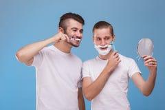 Dwa mężczyzna spojrzenie po one Jeden czyści jego zęby, i drugi goli jego brodę fotografia stock
