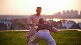 Dwa mężczyzna z sporty budową ciała tanczą capoeira outdoors, jeden one macha jego nogi przy inny zdjęcie wideo