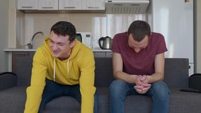 Dwa mężczyzny są uśmiechnięci Młodzi śmieszni faceci siedzą na leżance i śmiają się bardzo mocno przy dowcipem zbiory