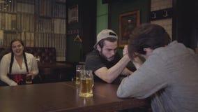 Dwa mężczyzny siedzi przy stołem w barze, angażującym w ręki zapaśnictwie Tłuściuchny kobiety obsiadanie w tle, emocjonalnie zbiory