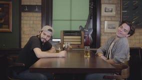 Dwa mężczyzny siedzi w prętowym pije piwie wpólnie Dziewczyna z piękną postacią przechodzi stołem, mężczyzny spojrzenia póżniej zbiory wideo