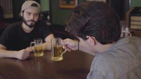 Dwa mężczyzny siedzi w prętowym pije piwie wpólnie Faceci ma zabawę wpólnie pije piwo Jeden mężczyzna patrzeje w zbiory