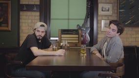 Dwa mężczyzny siedzi w prętowym pije piwie wpólnie Faceci Ma zabaw? Wp?lnie Przyjaciele widzią z pięknego dziewczyny omijania obo zbiory wideo