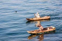 Dwa mężczyzny w schronów czółnach na Jeziornym Atitlan, Gwatemala fotografia stock