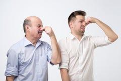 Dwa mężczyzny zakrywają ich nosy należnych zły odór fotografia royalty free