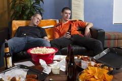 Dwa męczącego mężczyzna horyzontalnego, po tym jak oglądać bawi się grę na TV Zdjęcia Royalty Free