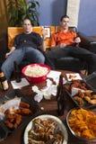 Dwa męczącego mężczyzna pionowo, po tym jak oglądać bawi się grę na TV Zdjęcie Stock