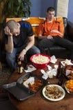 Dwa męczącego mężczyzna pionowo, po tym jak oglądać bawi się grę na TV Zdjęcie Royalty Free