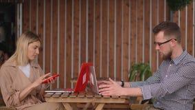 Dwa męski i żeńscy goście uliczna kawiarnia pracują z laptopami