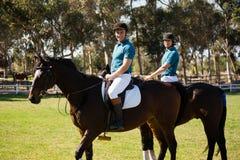 Dwa męskich dżokejów jeździecki koń w rancho Fotografia Stock