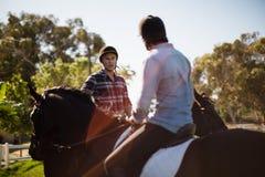 Dwa męskich przyjaciół jeździecki koń w rancho Fotografia Stock