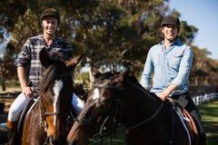 Dwa męskich przyjaciół jeździecki koń w rancho Fotografia Royalty Free