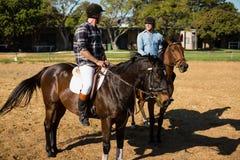 Dwa męskich przyjaciół jeździecki koń w rancho Obraz Stock