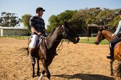 Dwa męskich przyjaciół jeździecki koń w rancho Zdjęcia Stock