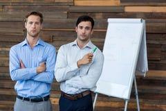 Dwa męskiego dyrektora wykonawczego w spotkanie pozyci przed trzepnięcie mapą obraz stock