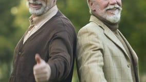 Dwa męskiego emeryta pokazuje aprobat, szczęśliwej i bezpiecznie starość, ubezpieczenie społeczne zbiory