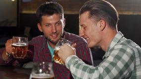 Dwa męskiego przyjaciela cieszy się pijący piwo przy lokalnym pubem zdjęcie wideo