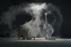 Dwa męskiego robią joga w pył chmurze w ciemnym pokoju Obraz Stock